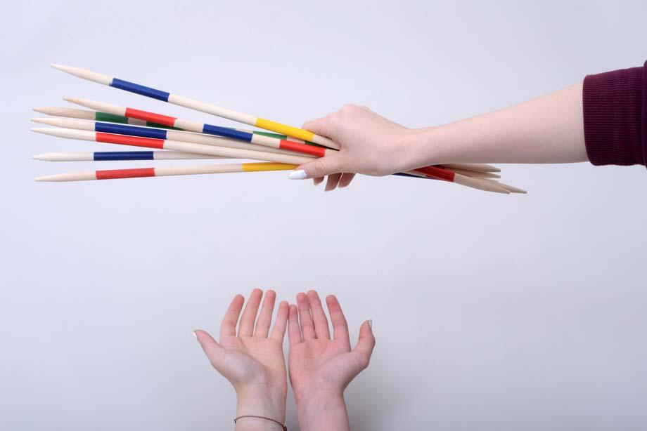 Eine Person gibt einer anderen Person Mikadostäbe in die leeren Hände