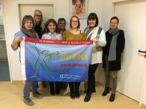 Kolleginnen von Kiss halten eine Fahne der Aktion von Terre de Femmes